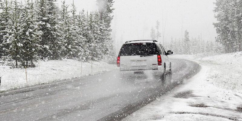 Weißes Auto fährt auf winterlicher Straße